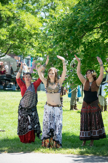 Arms Raised Belly Dance Belly Dancer Belly Dancing Celebration Costume Dance Day Enjoyment Fairgrounds Festival Front View Full Length Fun Grass Happiness Leisure Activity Lifestyles Outdoors Preformance Real People Skirt Standing Young Adult Young Women