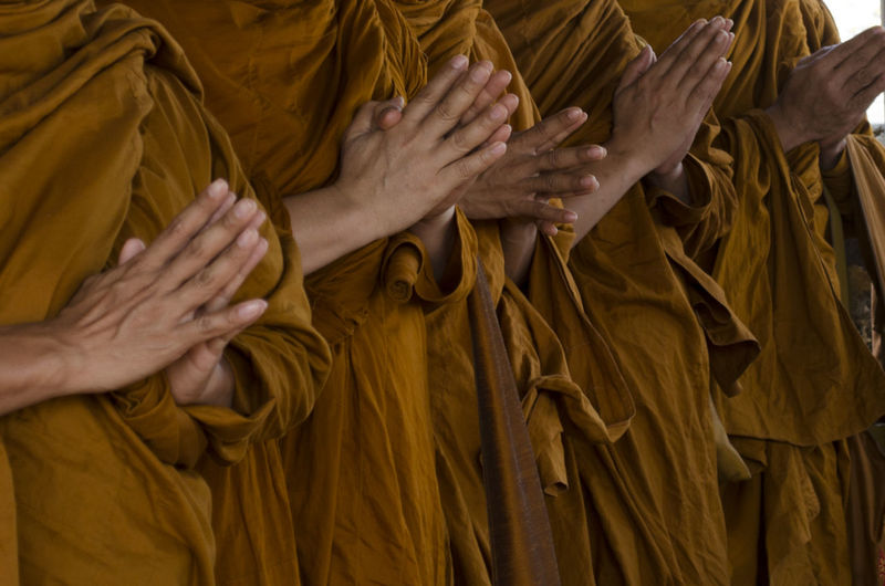 Midsection Of Monks Praying