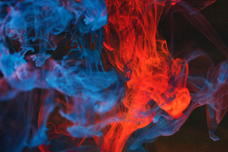 Close-up of red and blue smoke on black background