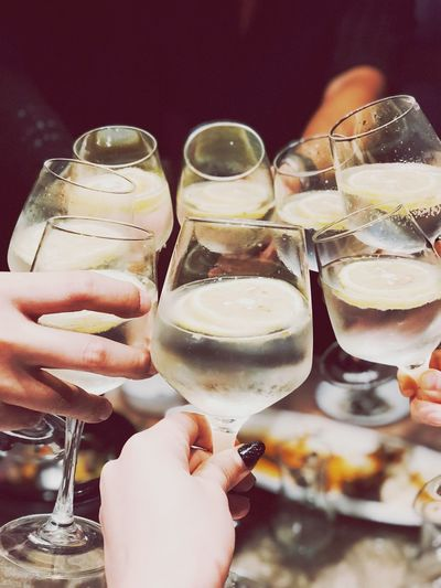 Cropped hands of people toasting drink in glasses