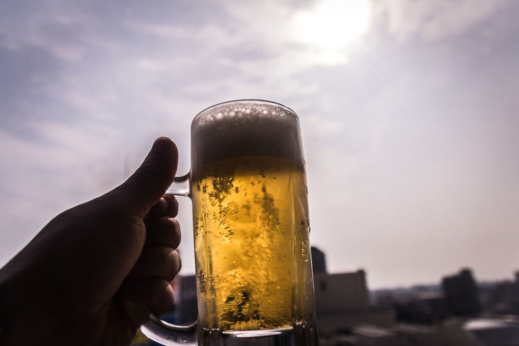 Close-Up Of Hand Holding Beer Glass Against Sky