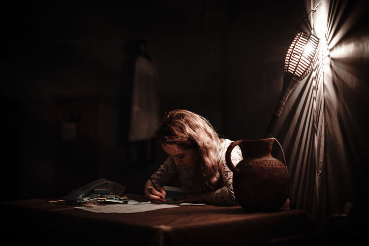 Portrait of woman reading book at home