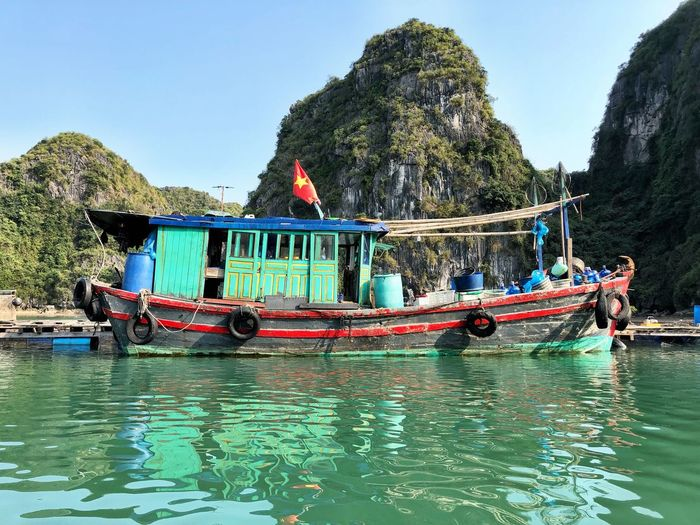 Boat in halong bay against mountains