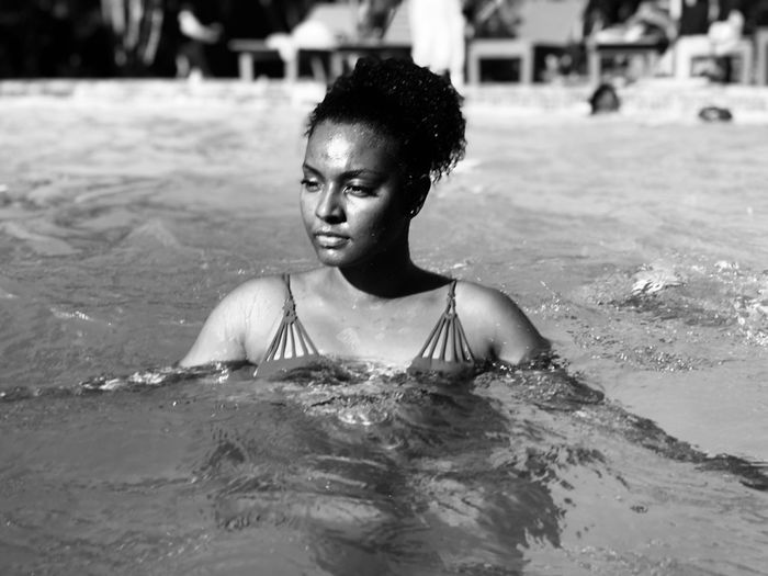 Woman looking away while swimming in pool