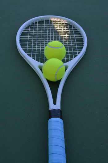 High angle view of balls and tennis racket at sports court