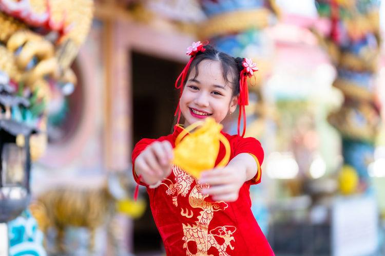 Portrait of smiling girl holding golden bag outdoors