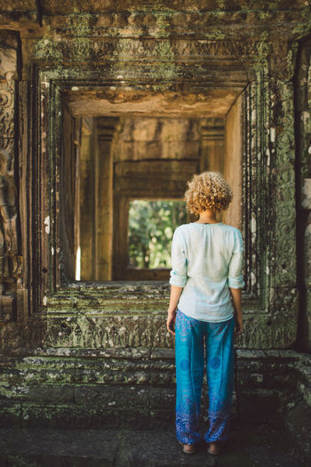 Rear view of young woman standing at angkor wat