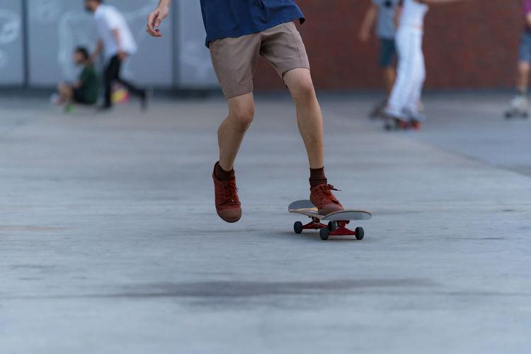 Low section of people walking on skateboard