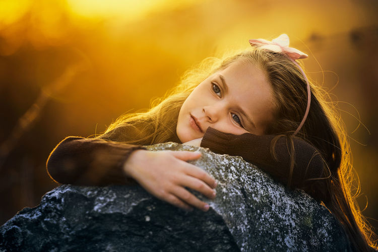 Close-up of sad girl leaning on rock during sunset