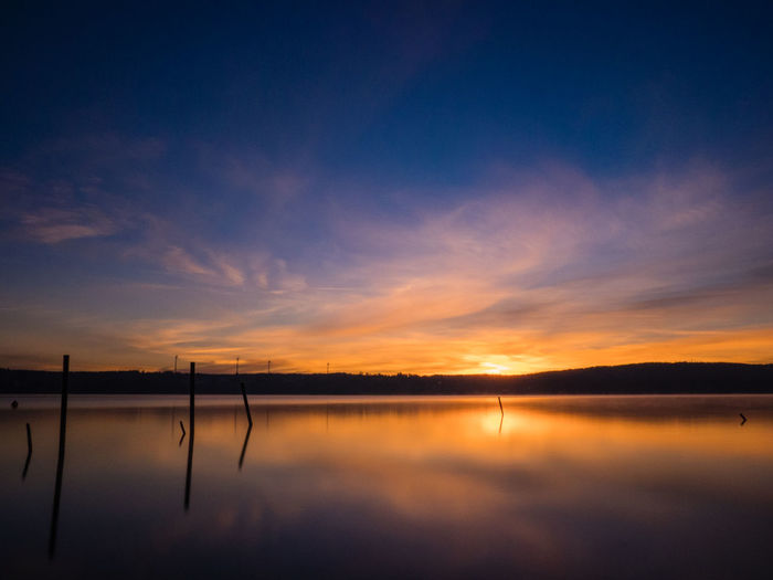 winter dawn over Starnberg LakeBeauty In Nature Blue Color Blue Sky Dawn Idyllic Lake Landscape Long Exposure Nature No People Orange Color Outdoors Reflection Scenics Silhouette Sky Teal And Orange Tranquil Scene Tranquility Water Blue Hour Landscapes