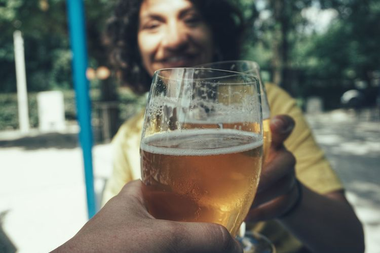 Close-up of cropped hand holding beer against smiling friend