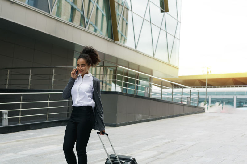 Close-up of businesswoman talking on phone while walking outdoors