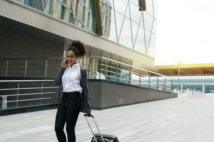 Females Lifestyle Mobile Phone Modern Travel Young Airport Businesswoman Call Cell Phone  Communication Formal Wear Luggage Mixed Race One Person Outdoors Public Smiling Suitcase Talking Technology Traveller