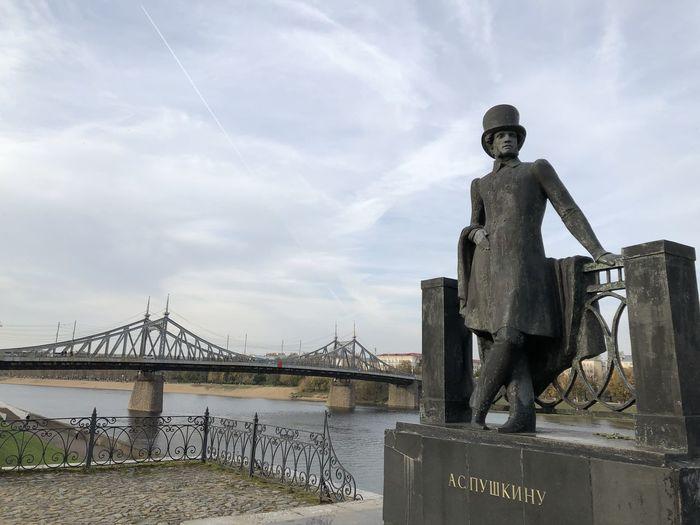 Statue of bridge over river against sky