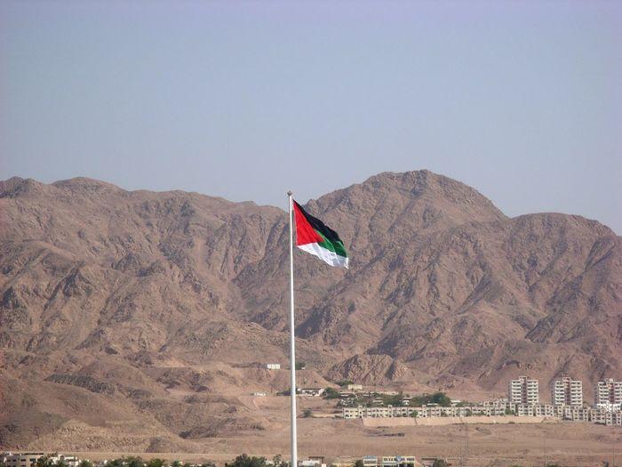 Flag on mountain against clear sky