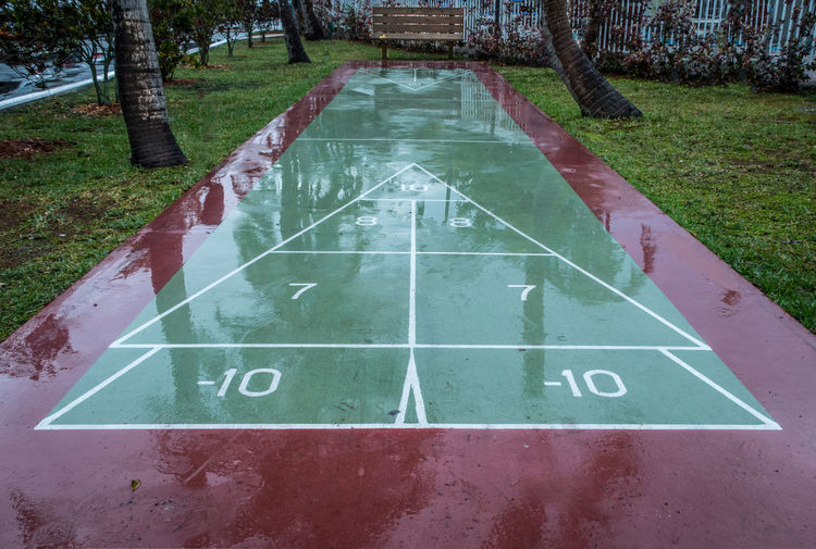 Bench Communication Day Direction Game Grass Grass Green Color No People Outdoor Games Outdoors Play Rain Rainy Days Road Road Marking Road Sign Sign Street Text Tree Trees Water Western Script Wet