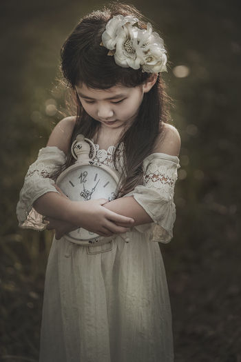 Close-Up Of Girl Holding Clock