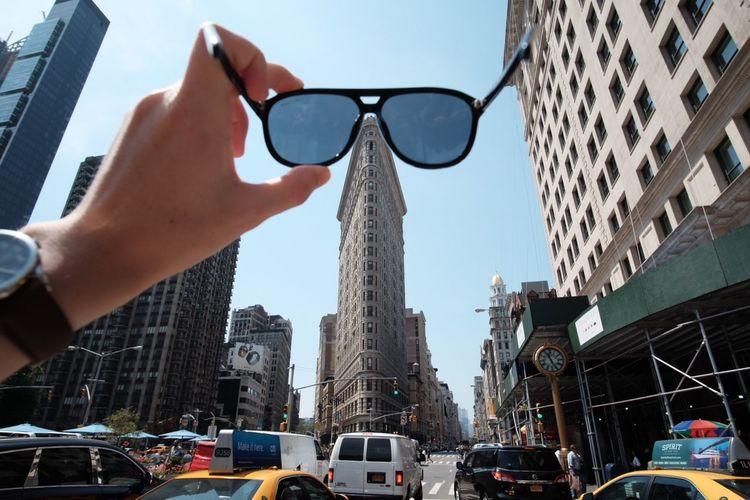 Cropped hand with sunglasses against cars and flatiron building in city