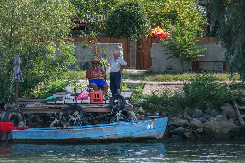 Danube Delta Danube Adult Architecture Boat Bonding Building Exterior Childhood Day Full Length Leisure Activity Lifestyles Men Mode Of Transport Nature Nautical Vessel Oar Outdoors Real People Sailing Sitting Togetherness Transportation Tree Two People Water Waterway To Sulina Women