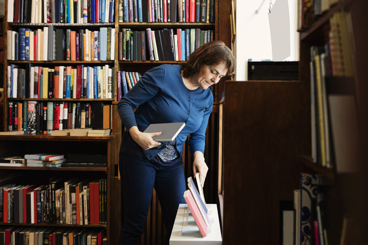 Full length of woman reading book while standing in library