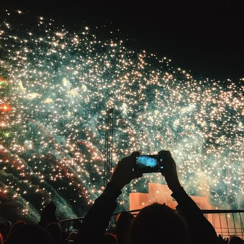 Man Photographing Fireworks From Smart Phone At Night