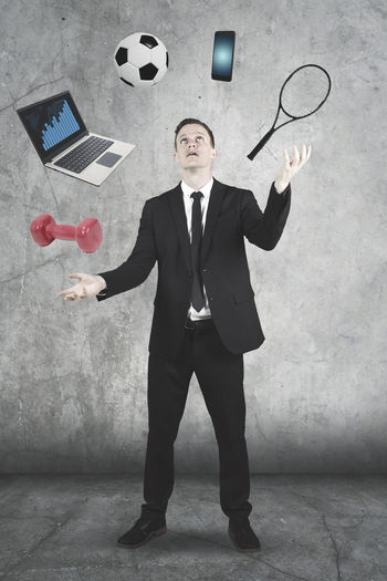 Businessman Juggling Technologies And Sports Equipment Against Wall