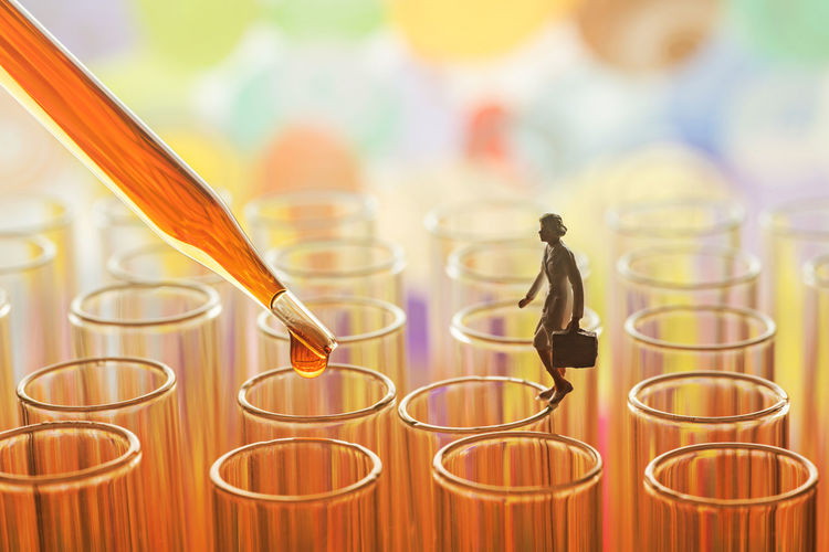 Close-up of pipette by figurine on test tubes
