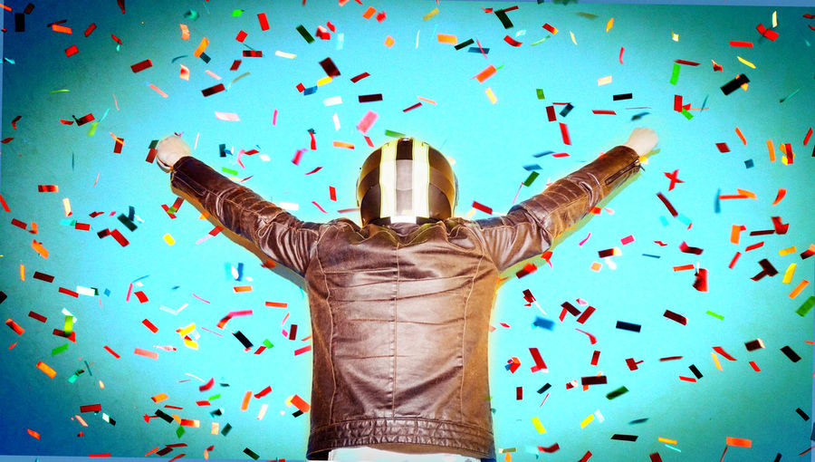 Confetti Falling On Biker With Arms Raised Standing Against Turquoise Wall