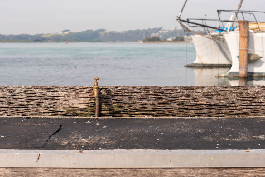 Fish cleaning bench and tap with boats behind Day Focus On Foreground Lake Mode Of Transportation Moored Nature Nautical Vessel No People Outdoors Pier Sailboat Sky Sunlight Tranquil Scene Tranquility Transportation Water Wood - Material