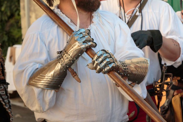 Midsection of man holding sword outdoors