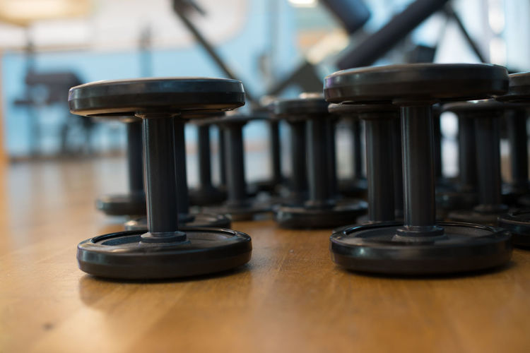 Close-Up Of Dumbbells On Wooden Floor At Gym