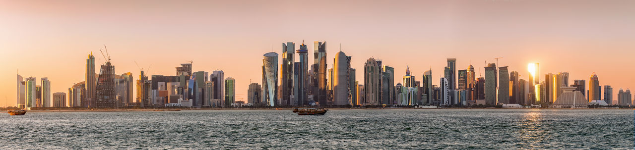 The skyline od Doha, Qatar, during sunset Construction Doha Middle East Modern Tourist Attraction  Travel Bay Building Capital Cities  City Cityscape Corniche Downtown District Landscape Office Building Exterior Panoramic Qatar Sky Skyscraper Sunset Tower Travel Destinations Urban Urban Skyline Water
