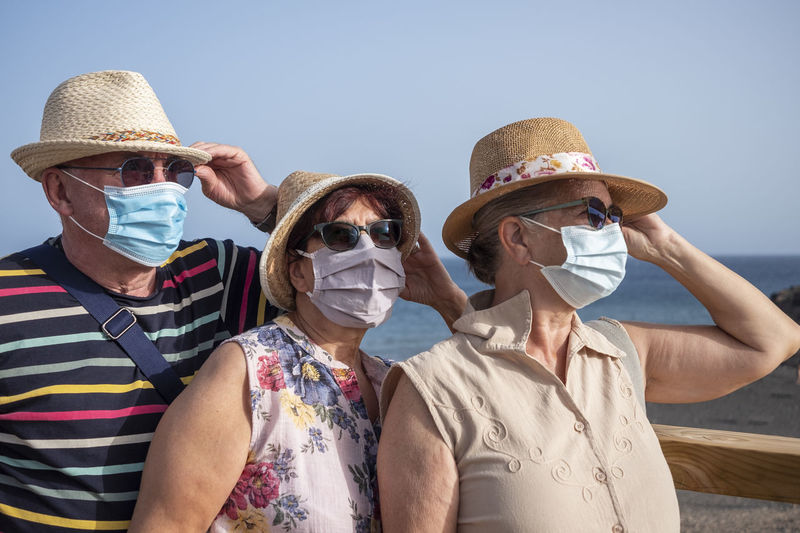 Senior friends wearing mask against sea