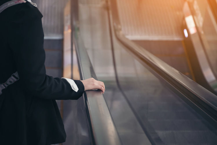 Midsection of man standing on escalator