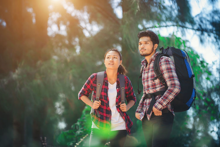 Male And Female Hikers Carrying Backpacks In Forest