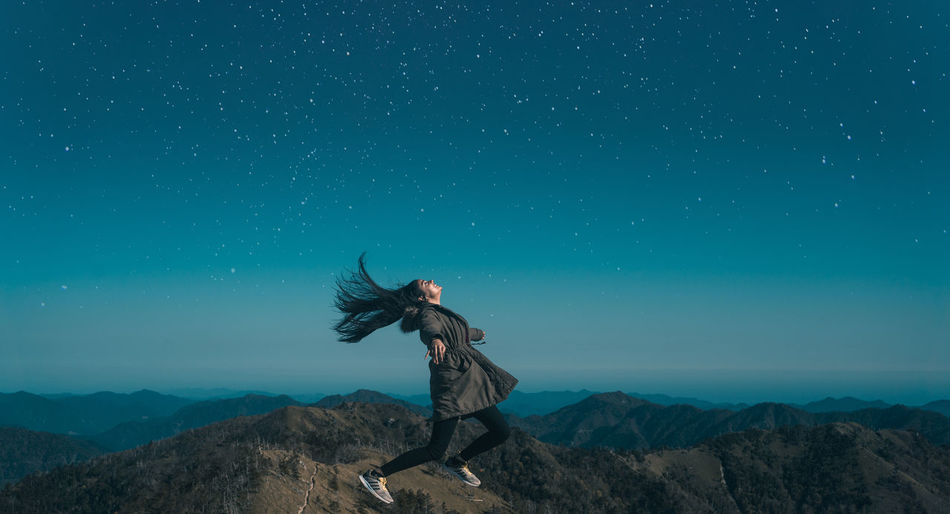 // flying high // One Person Real People Mountain Sky Lifestyles Leisure Activity Blue Beauty In Nature Full Length Scenics - Nature Nature Tranquil Scene Human Arm Men Tranquility Standing Non-urban Scene Mountain Range Clothing Arms Raised Stars Joy Women Power Levitation