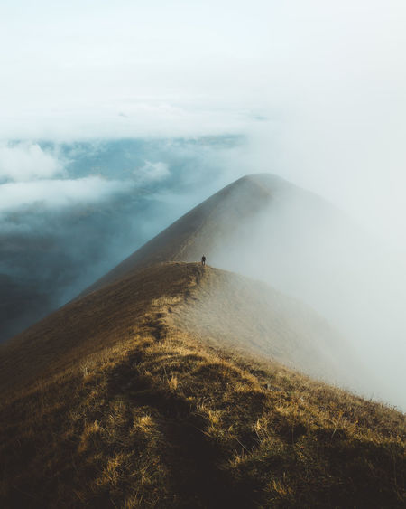 Scenic view of foggy mountains against sky with person