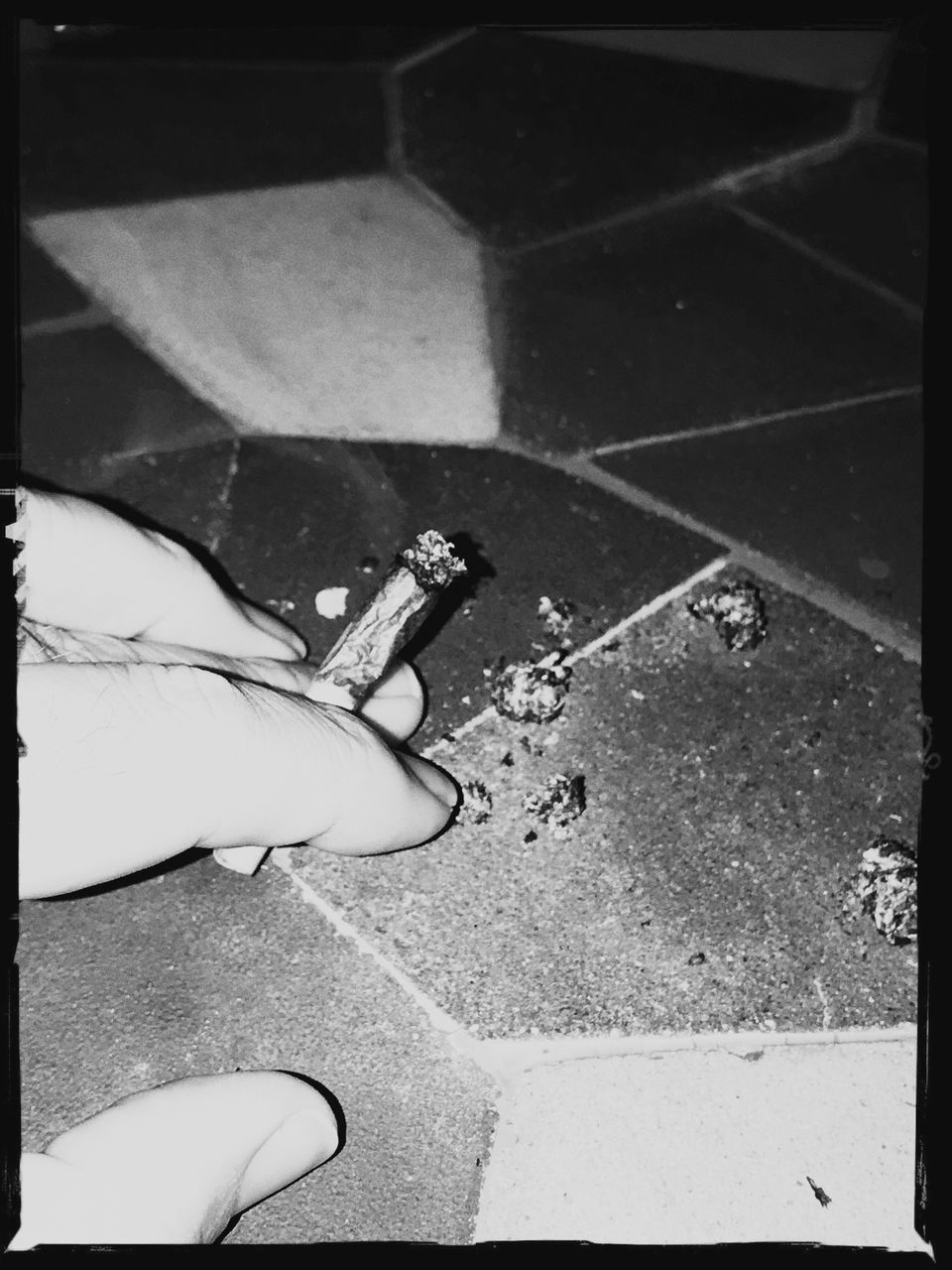 LOW SECTION OF PERSON HOLDING CIGARETTE ON FLOOR