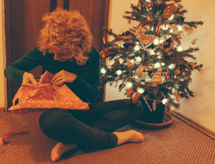 Portrait of woman unwrapping christmas gift