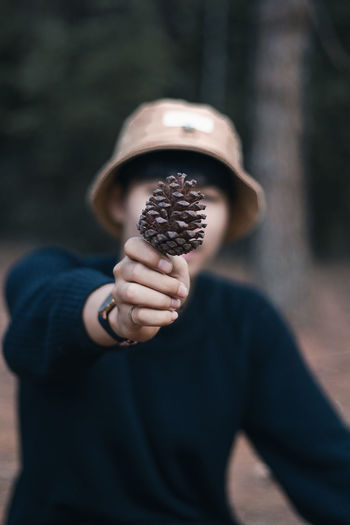 Close-up of man covering face with pine cone