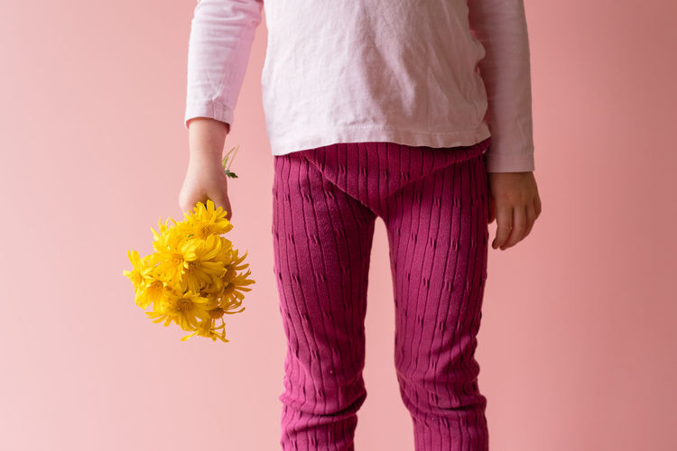 Midsection of woman holding yellow flowers against pink background