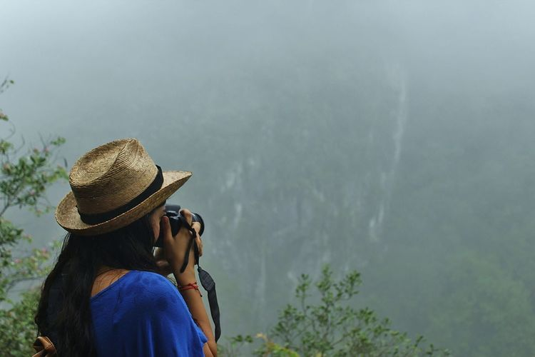 Rear view of woman photographing mountains in foggy weather