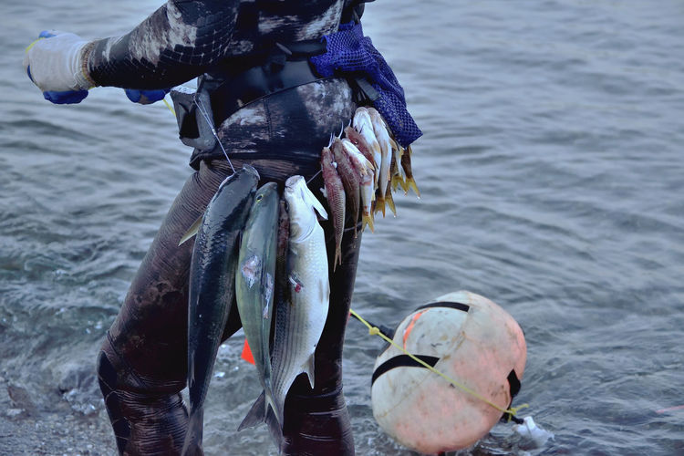 Midsection of fisherman with fish tied on waist in sea