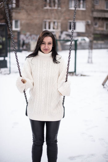 Portrait of young woman swinging in snow covered playground
