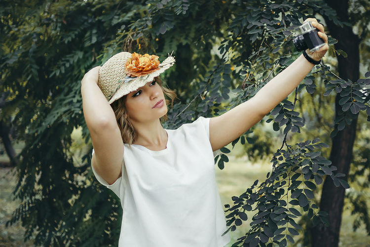 Dana Hat Adult Beautiful Woman Beauty In Nature Casual Clothing Day Freshness Front View Growth Holding Leisure Activity Lifestyles Nature One Person One Young Woman Only Outdoors People Photography Real People Selfie Standing Tree Women Young Adult Young Women