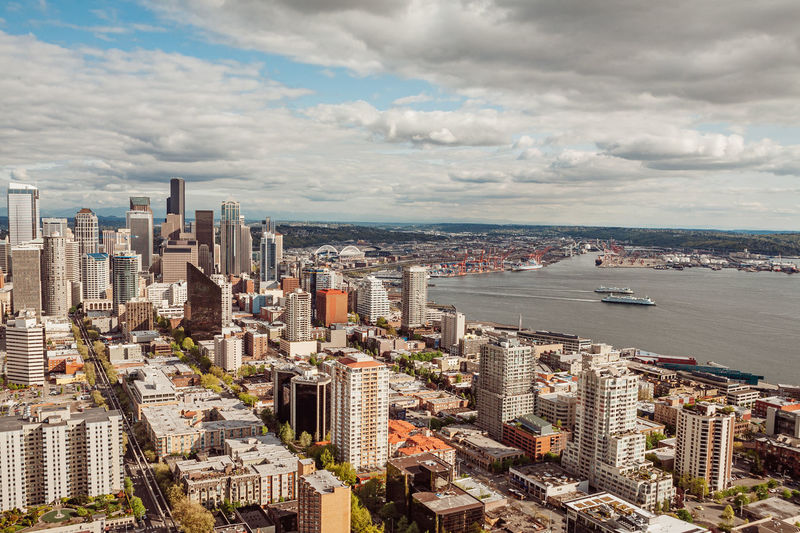 High angle view of buildings and port of seattle and two ferries against clouds and blue sky