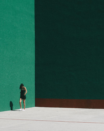 Young woman walking by green wall