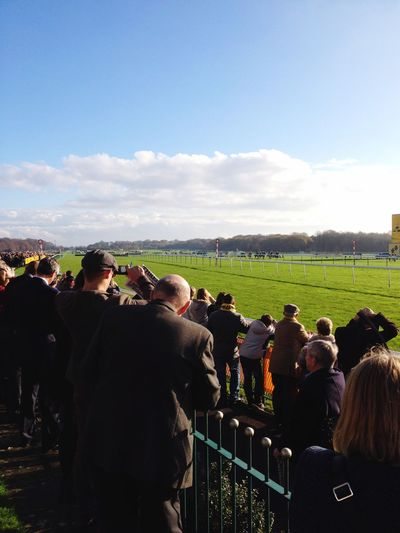 Spectators Standing In Stadium Looking At Horseracing Track