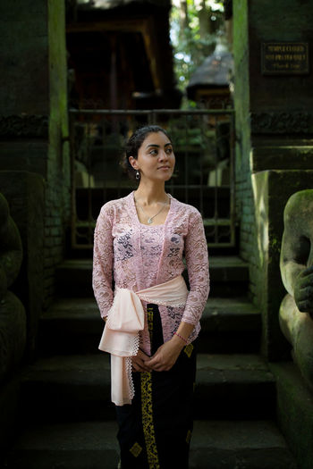 Young woman looking away while standing against building