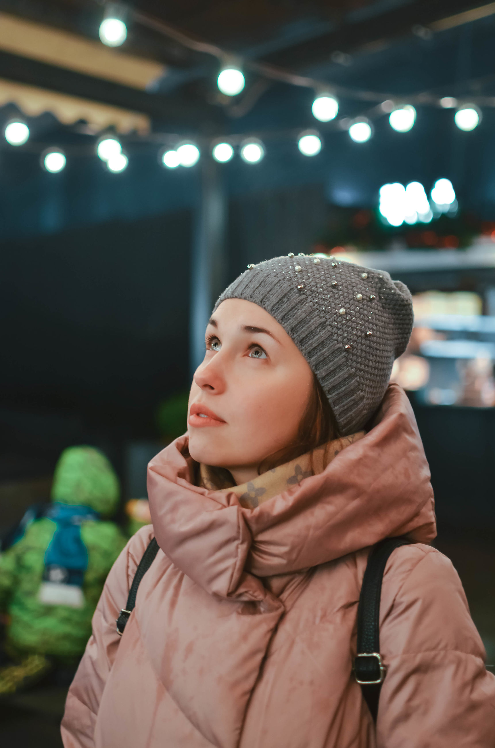 one person, real people, clothing, focus on foreground, looking away, lifestyles, looking, leisure activity, portrait, indoors, winter, illuminated, young adult, warm clothing, hat, women, standing, headshot, front view, contemplation, beautiful woman, scarf, hairstyle